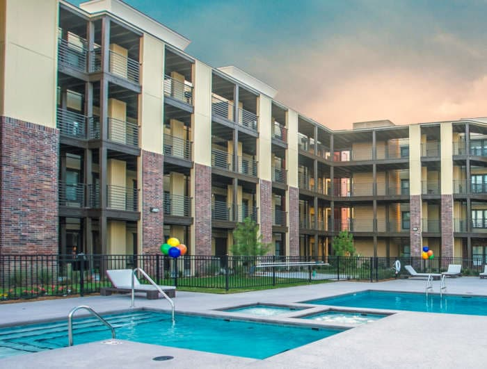 Four story apartment buildings with elevators surround a swimming pool at Crown Win River Apartments in Tulsa Oklahoma